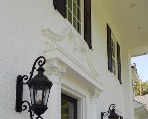 Early Classical Revival (front door, broken pediment, lanterns, shutters)